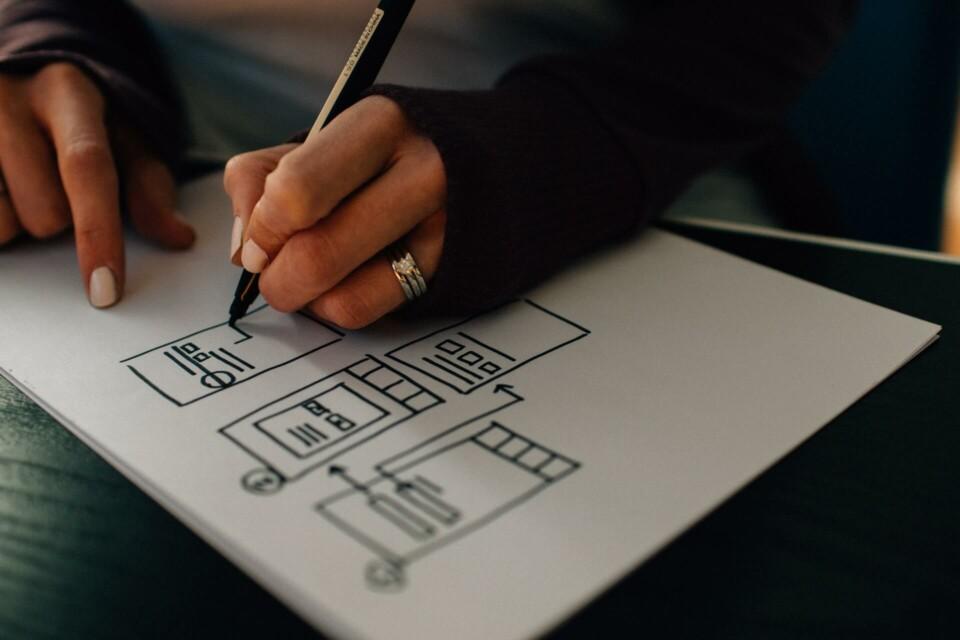 mulher desenhando à mão um wireframe