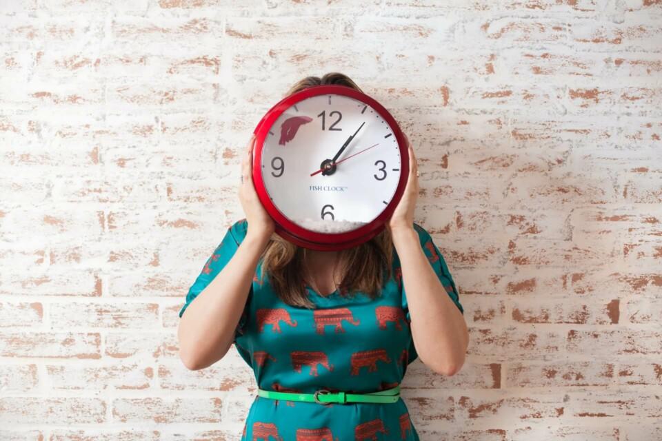Mulher segurando relógio vermelho cobrindo seu rosto