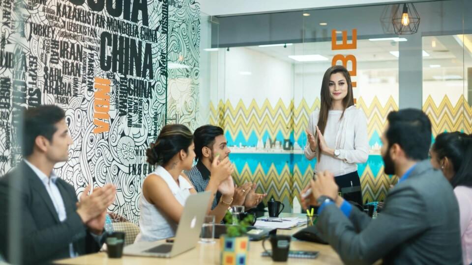 mulher em pé em sala de reunião com colegas
