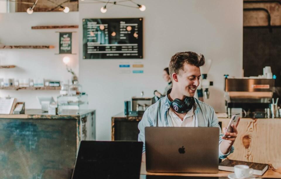 Homem sorrindo em frente a notebook enquanto mexe no celular