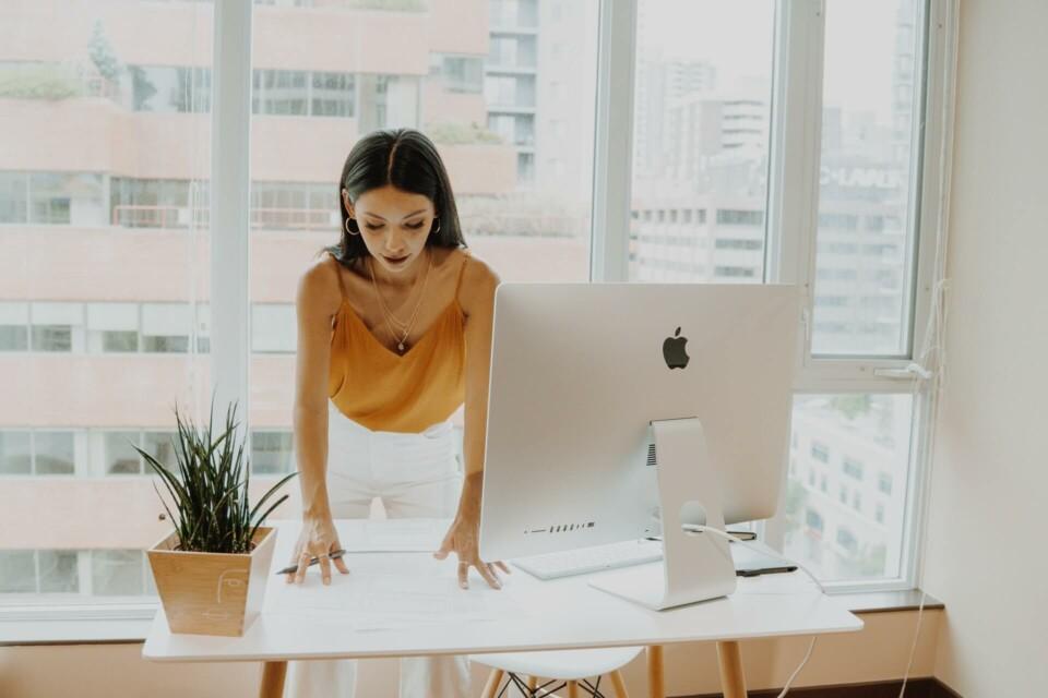 Mulher em pé organizando papéis próxima a um computador