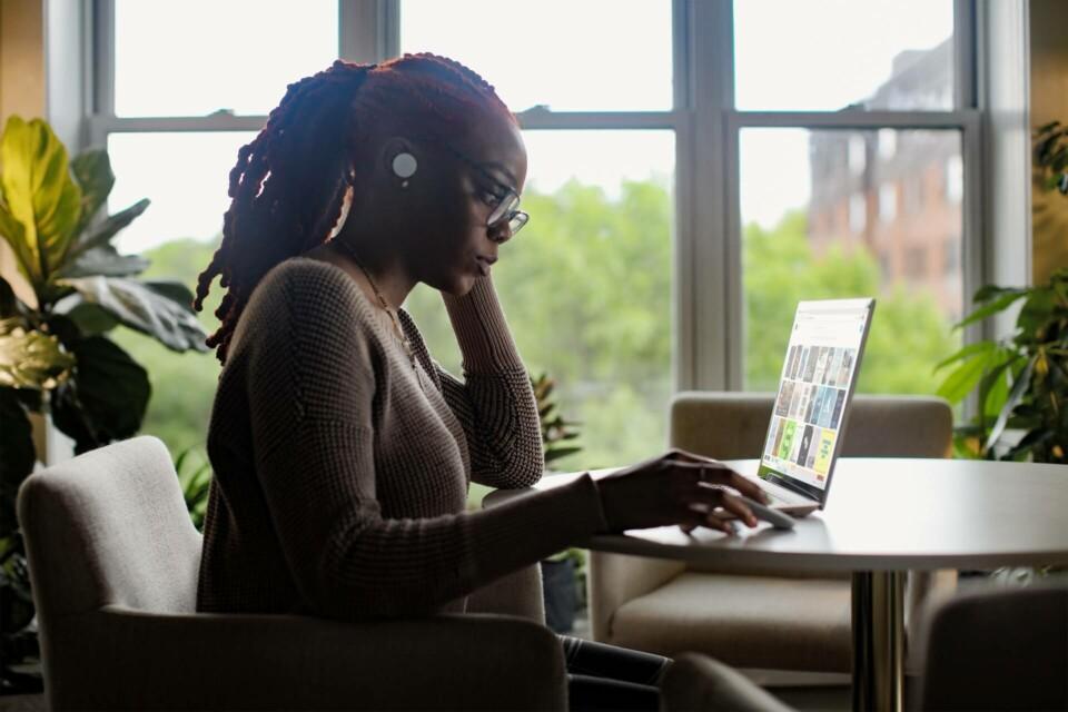 Mulher negra trabalhando com fones de ouvido e computador